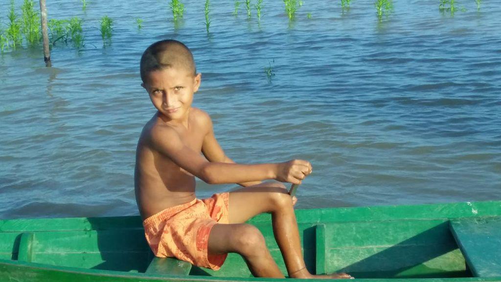 menino remando canoa lago