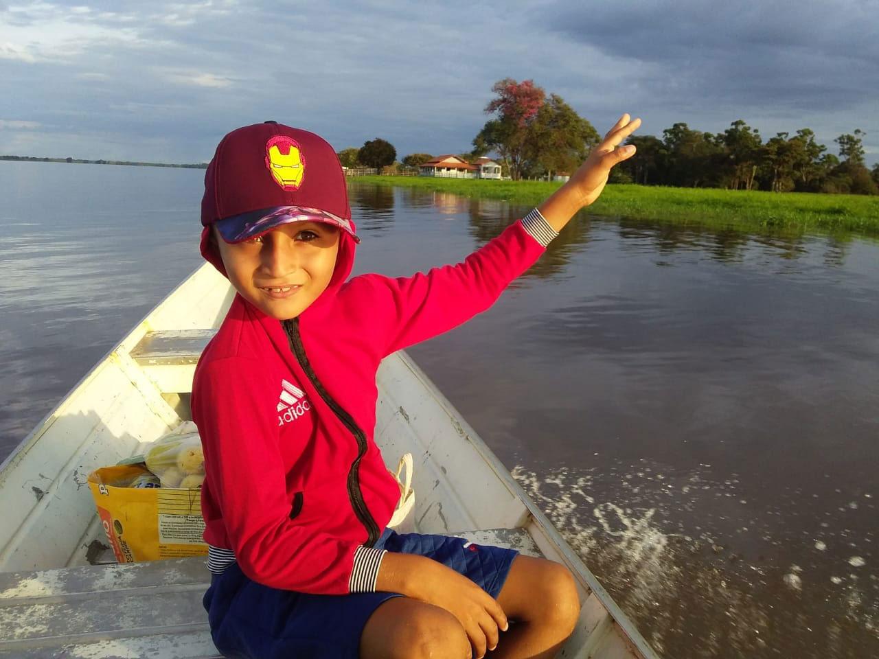 menino dentro canoa navegando rio