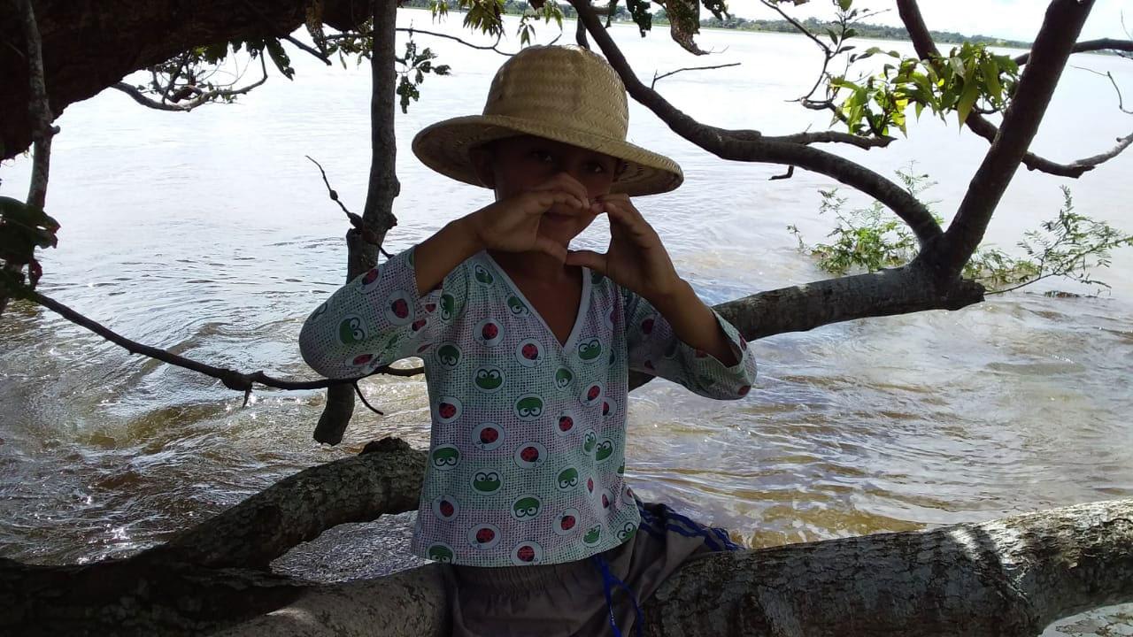 menino sentado galho árvore fazendo sinal coração mãos