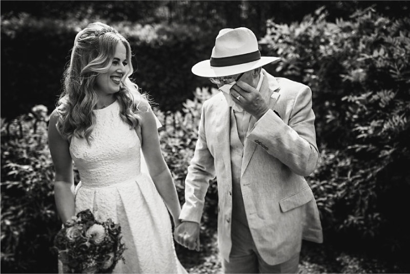 pai enxuga as lágrimas ao ver a sua filha vestida de noiva