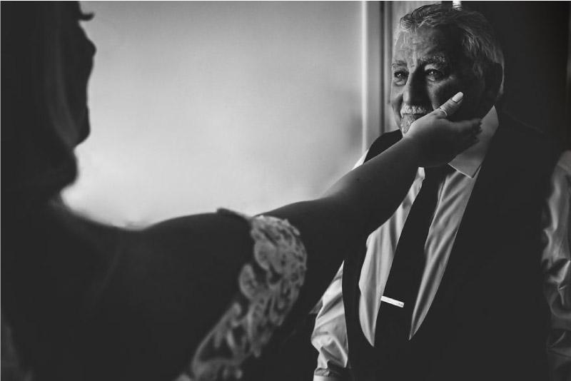 filha coloca a mão no rosto do pai quando ele a vê vestida de noiva