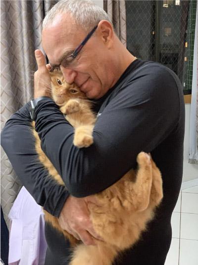 homem abraçando gato