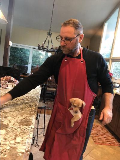 homem com cachorro no avental