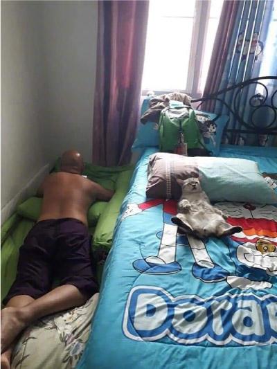 homem dormindo no chão e gato na cama