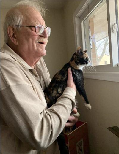 homem na janela segurando gato