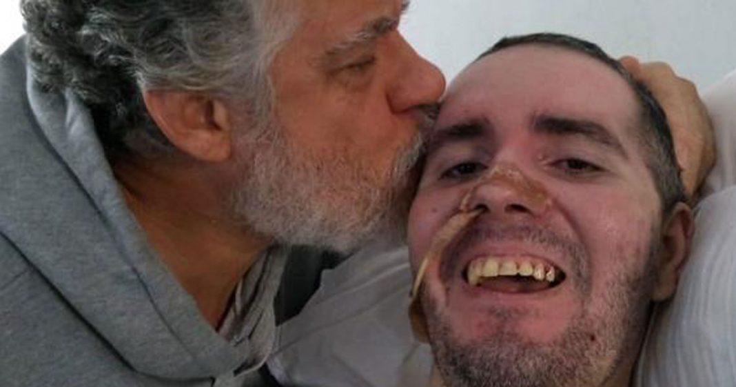 pai beija cabeça filho deitado leito hospital