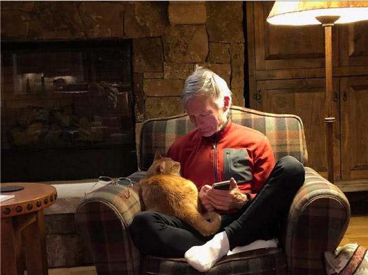 homem lendo com gato no colo