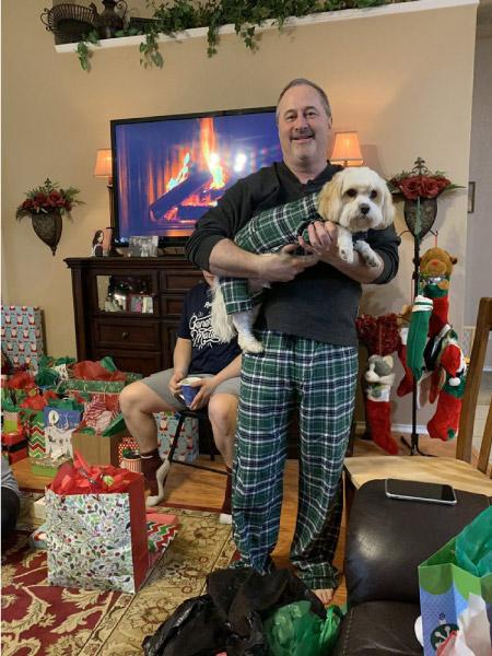 homem em pé com cachorro no braço