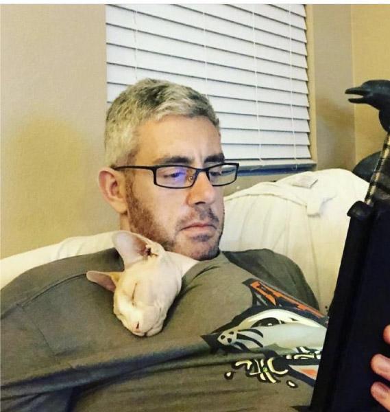 homem com gato dentro da blusa