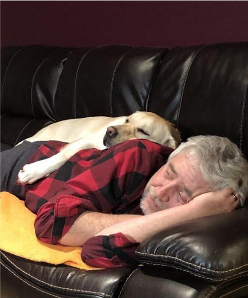 Homem deitado no sofá com cachorro