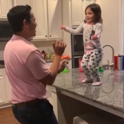 Pai e filha dançam na cozinha