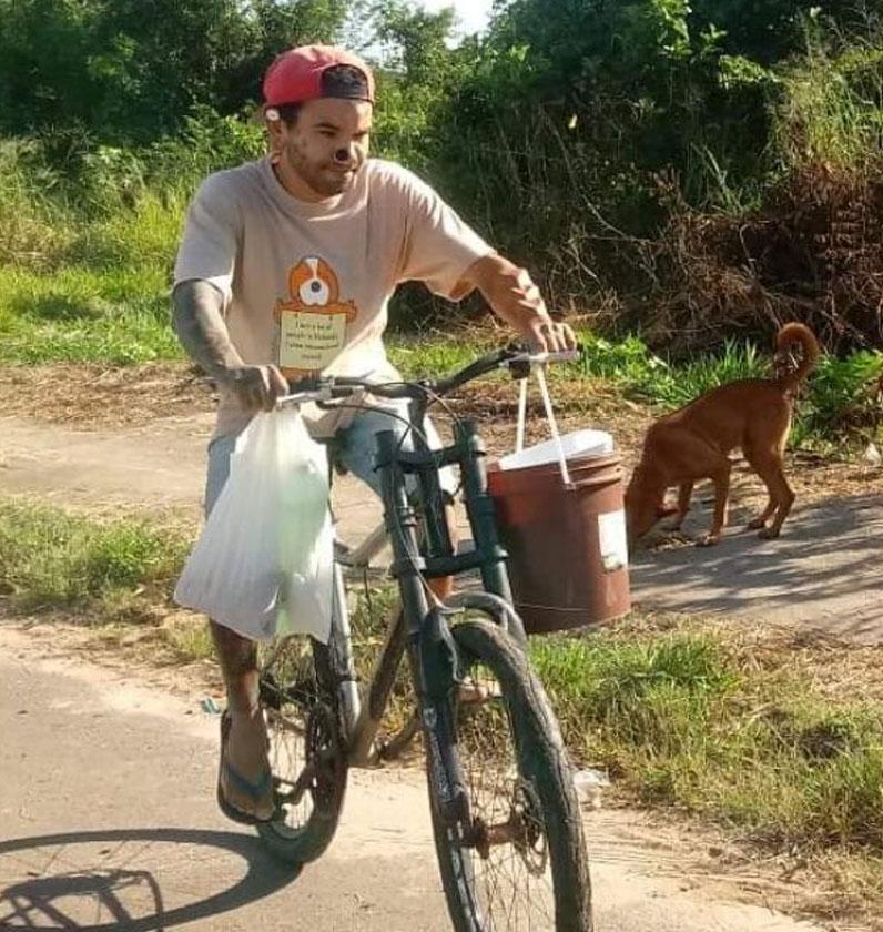 jovem andando bicicleta carregando ração alimentar cães rua