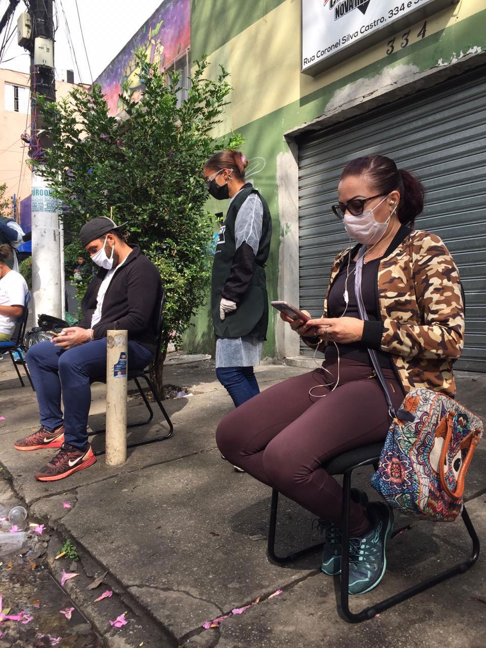 moradores heliópolis sentados cadeiras rua acessando wi-fi gratuito