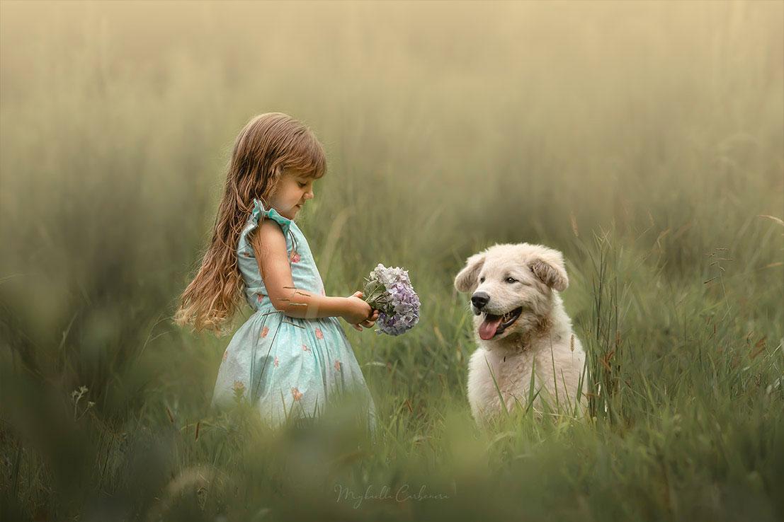 menina segurando buquê ao lado cachorro campo