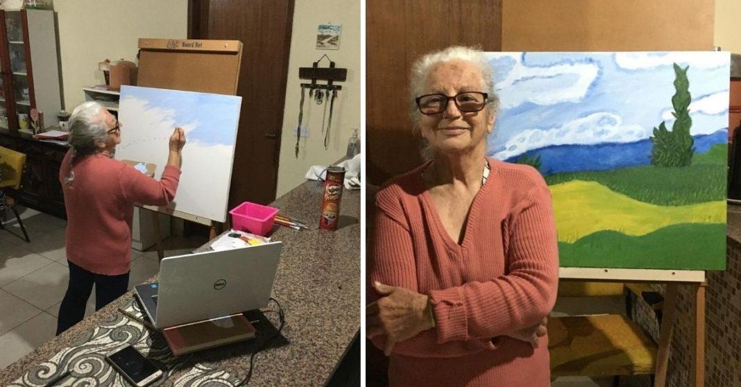 Avó pintando quadro em tela no cavalete que ganhou dos netos e acompanhando orientações de professor no notebook à sua frente e avó de braços cruzados posando para foto à frente do quadro que pintou na tela com gramado, rio e árvore