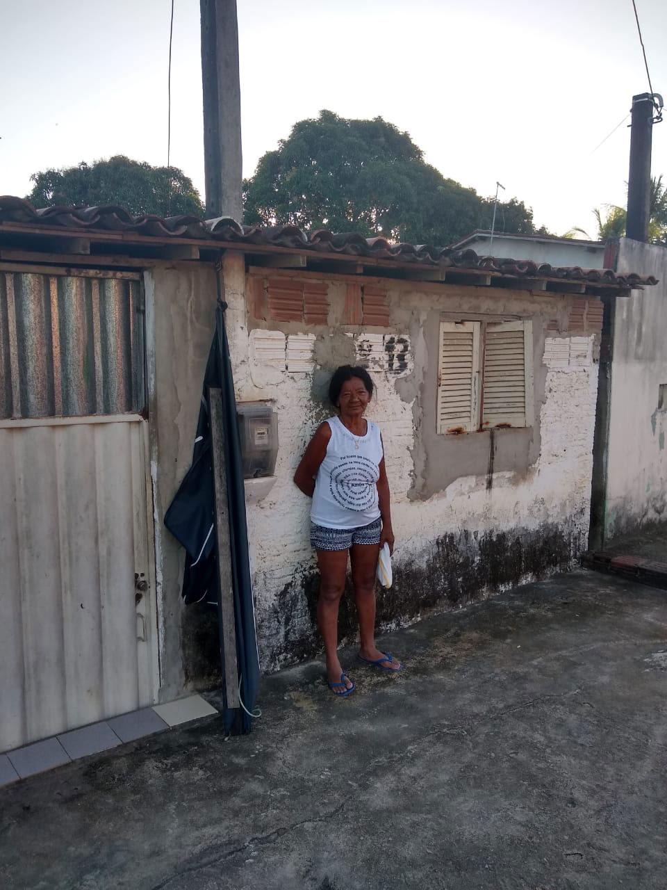 mulher em frente casa sem reboco