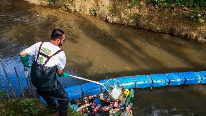 homem retira lixo rio parado ecobarreira