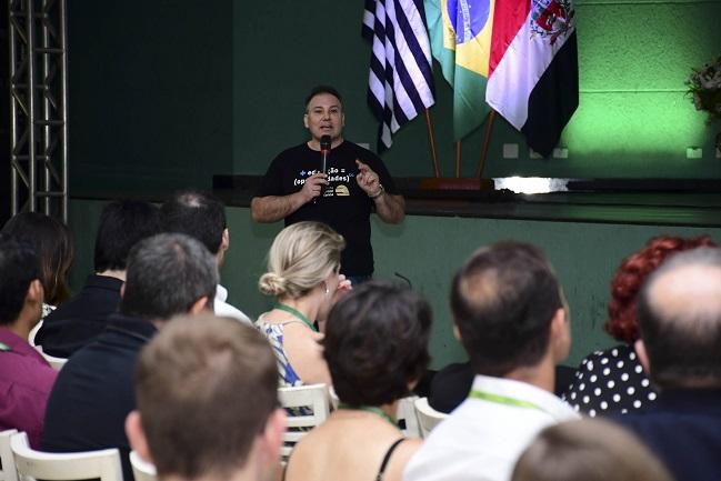Homem dando palestra sobre educação para plateia