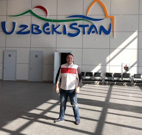 Homem em aeroporto com emblema do Uzbequistão ao fundo