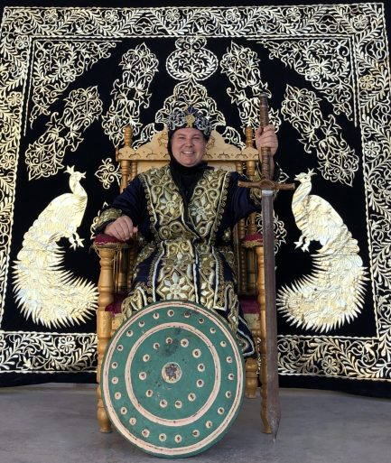 Homem sentado em trono com roupa de rei e escudo e tapete atrás