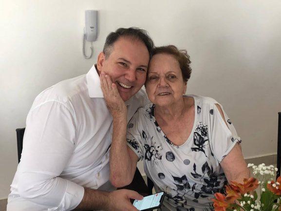 Homem abraçado com idosa
