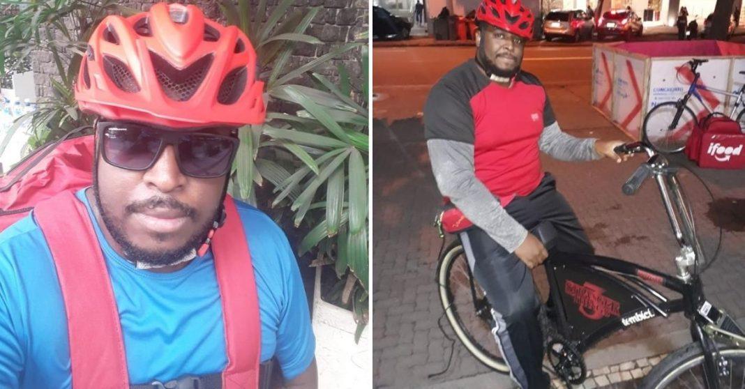 Homem negro de óculos escuros, camisa azul, com capacete de ciclista e mochila de entrega de comidas e ao lado ele na bicicleta