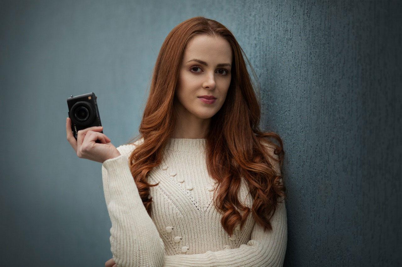 fotógrafa segurando câmera encostada parede azul