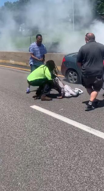 homem retirando motorista carro em chamas