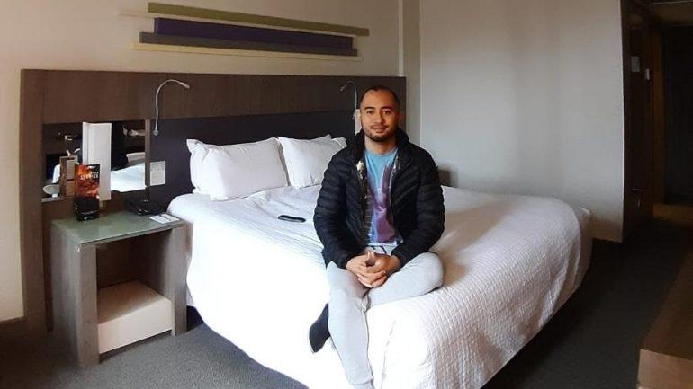 Profissional de saúde sentado em cama de hospedagem em hotel