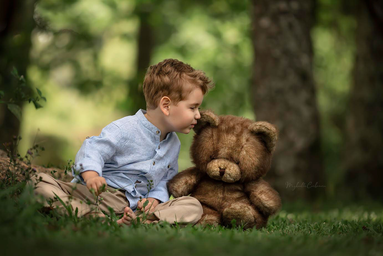 menino sentado grama beijando urso pelúcia