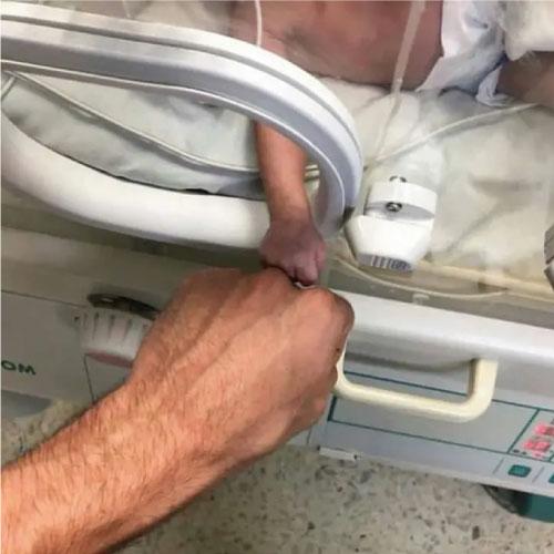enfermeiro tocando mão de bebê