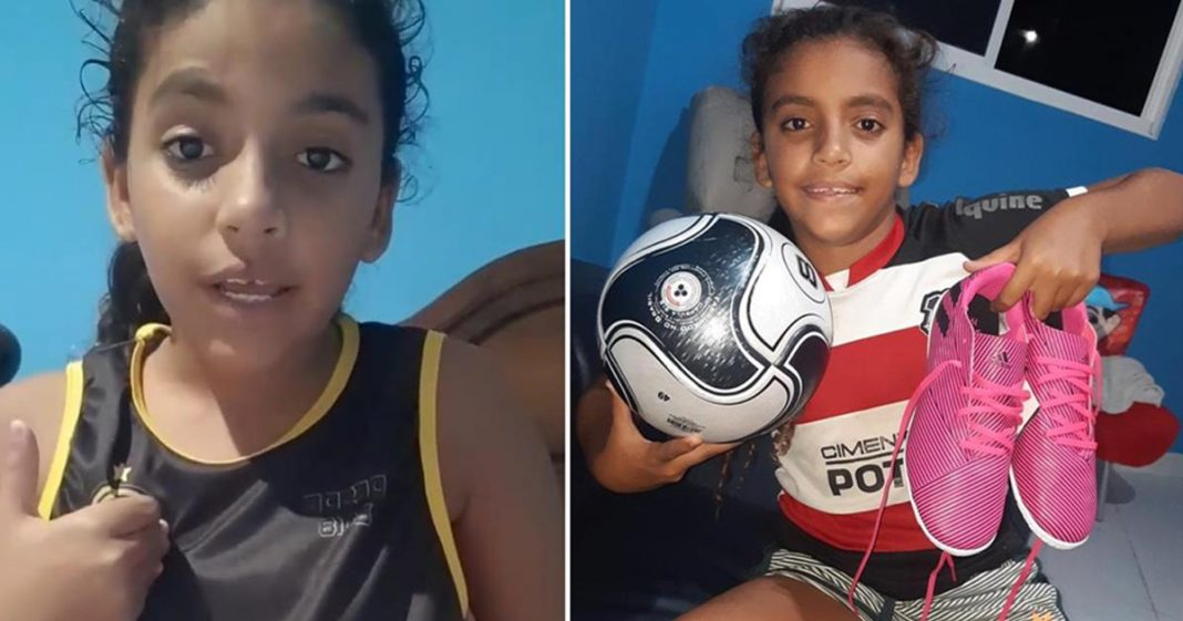 menina sorrindo segurando bola futebol chuteira
