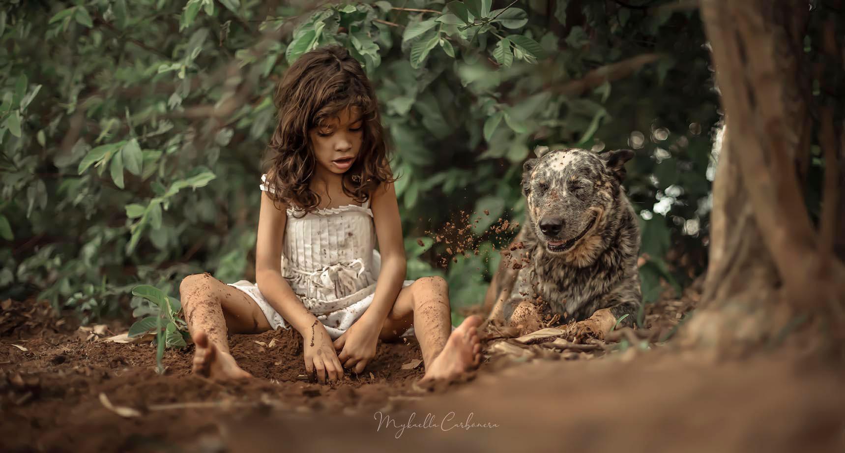 menina cavando areia ao lado cachorro