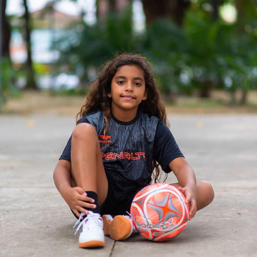 menina sentada quadra futebol segurando bola