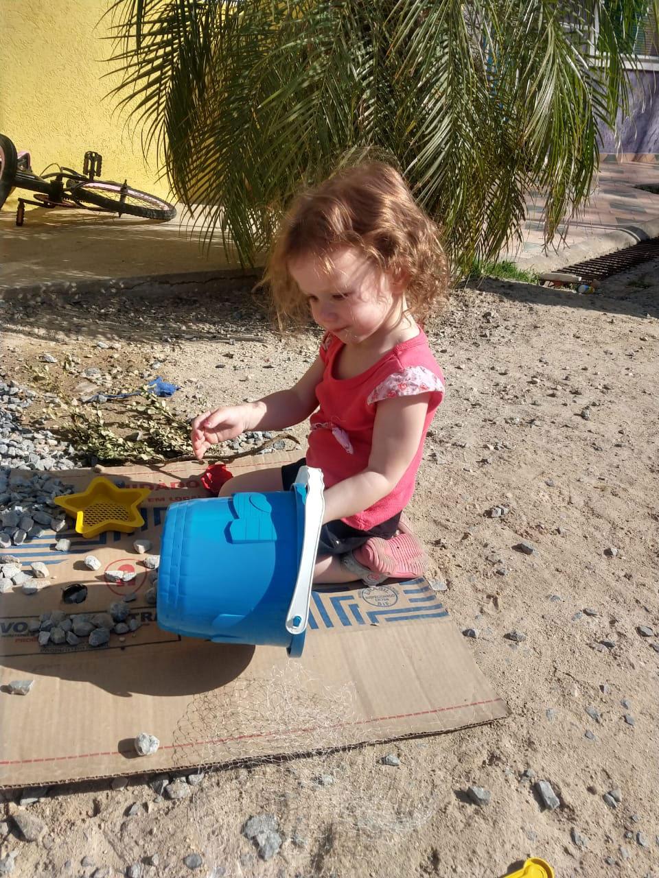 menina brincando balde areia
