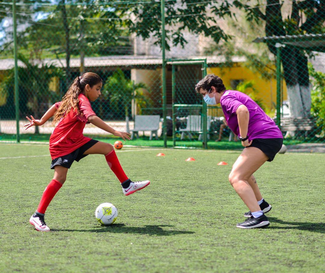 menina treinando futebol gramado junto treinadora