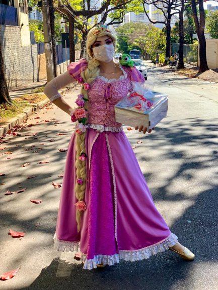 Mulher vestida de princesa com kit infantil na mão