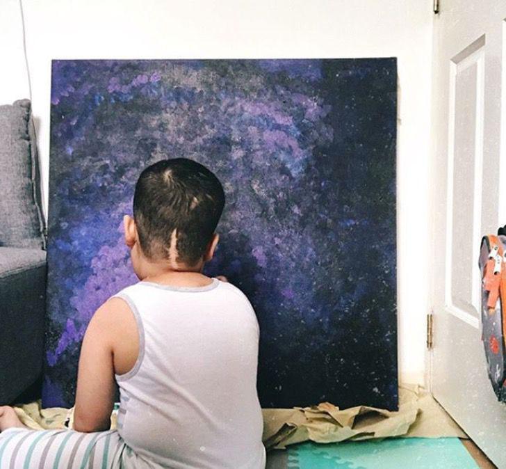 menino pintando quadro sentado chão