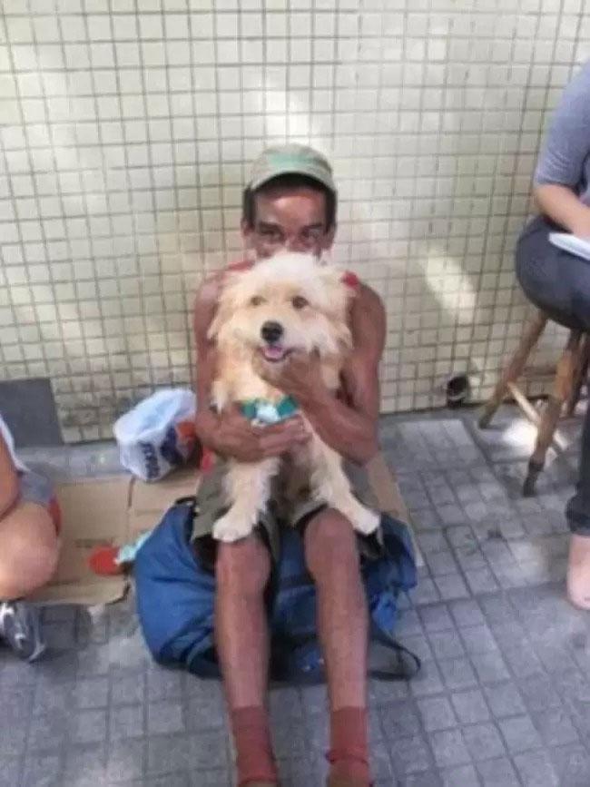 morador rua segurando cão sentado calçada