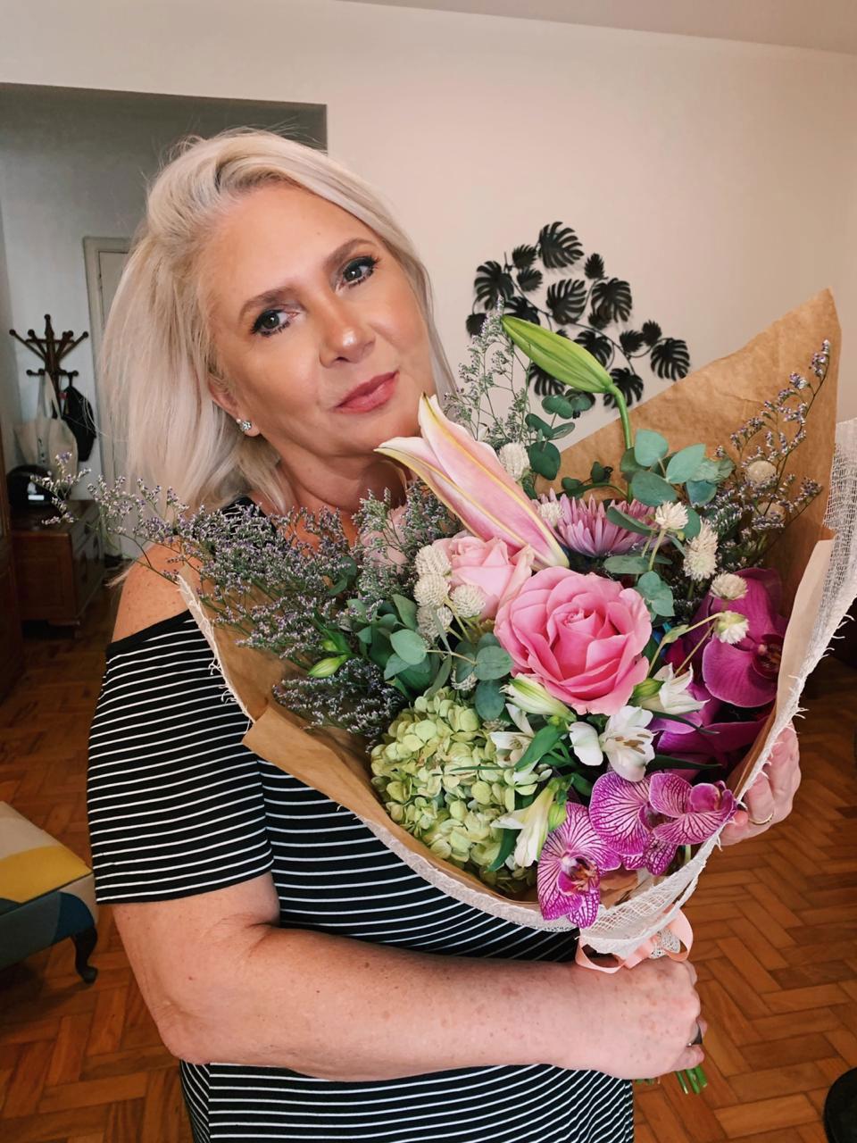 mulher segurando buquê plantinhas flores