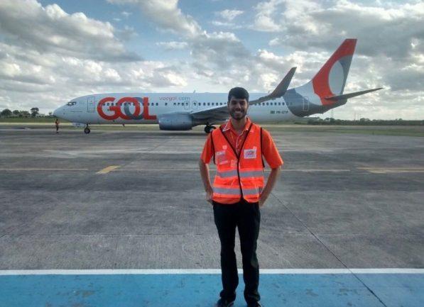 Garoto com uniforme de trabalho de pista de aeroporto em frente a avião