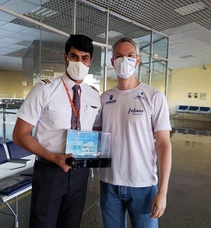 Piloto de avião com troféu ao lado de professor