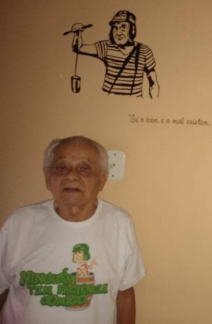 Idoso com camisa do Chaves e na parede um desenho do Chaves