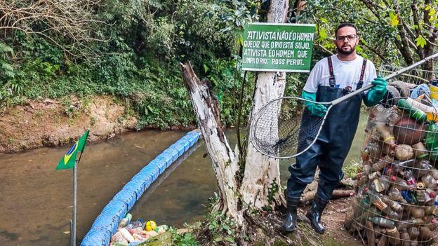 homem retira lixo rio preso ecobarreira
