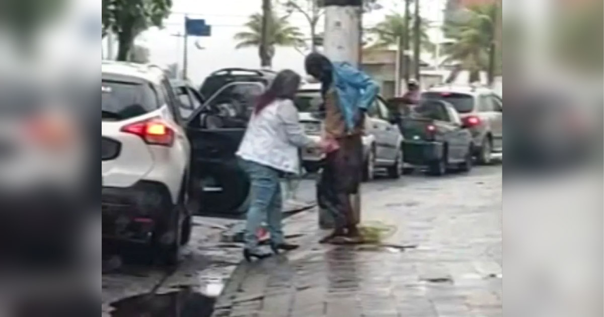 mulher ajuda morador de rua.