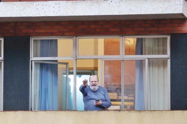 idoso na varanda do apartamento