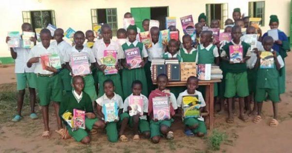 crianças mostram livros doados
