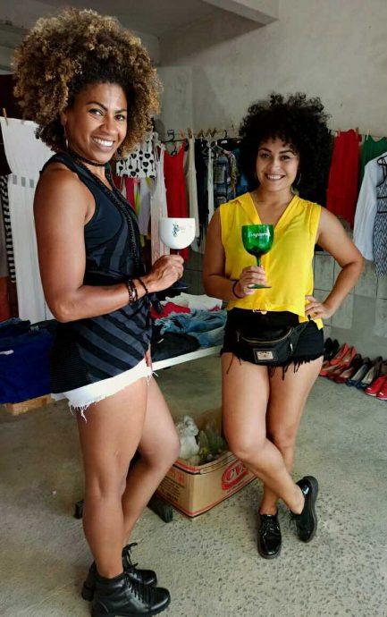 Imagem de brechó com varais de roupas penduradas em garagem e duas mulheres brindando