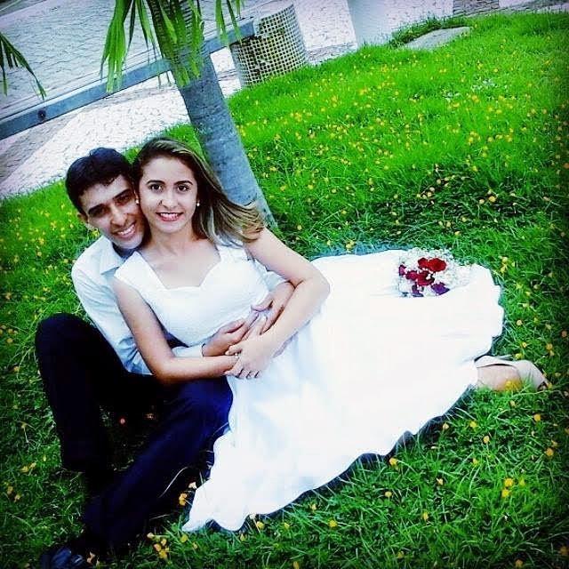 casal noivos sentados abraçados grama jardim