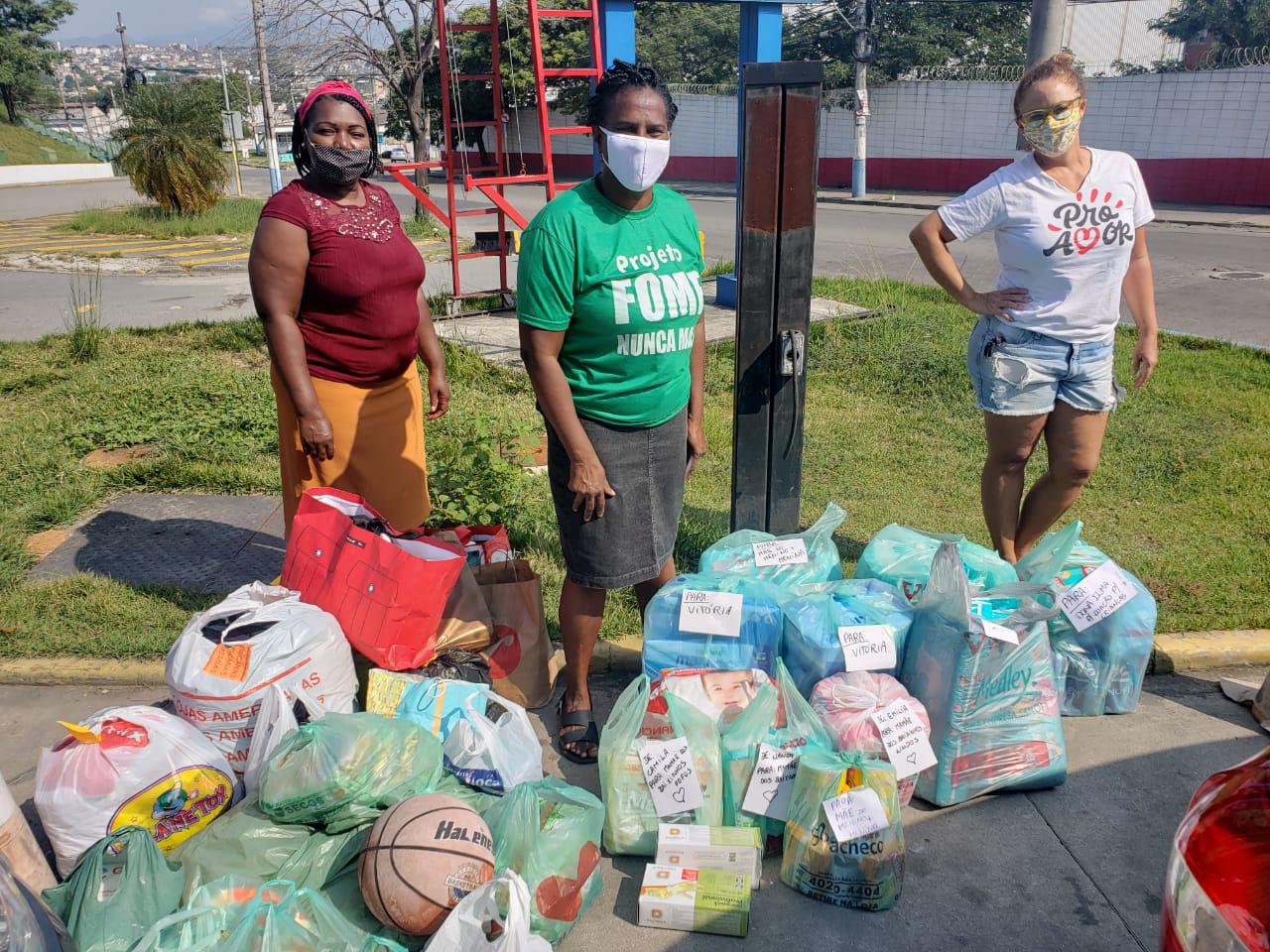 três mulheres negras cercadas cestas básicas